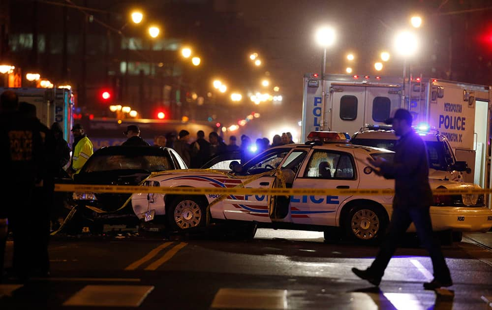 Law enforcement officers investigate the scene involving at least one wrecked DC Metro police car, in the 1100 block of H Street NE