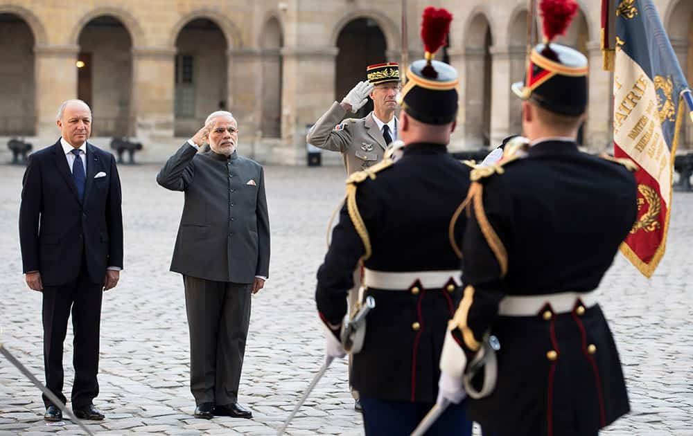 Prime Minister Narendra Modi, accompanied by French Foreign Minister Laurent Fabius, salutes the French flag during a welcoming ceremony in the courtyard of the Hotel des Invalides in Paris.