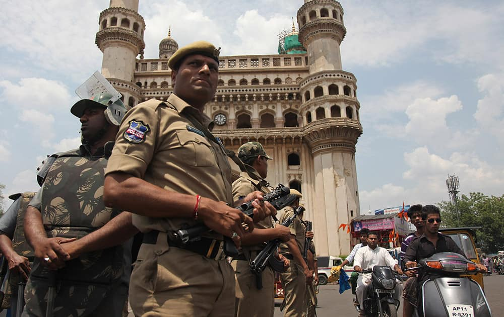 Policemen stand guard in front of the landmark Charminar during Friday prayers at Mecca Masjid in Hyderabad. Security was increased as a preventive measure on the first Friday following the killing of five prisoners, including one accused of terrorism, when, according to the police, they tried to escape from a police van on Tuesday.