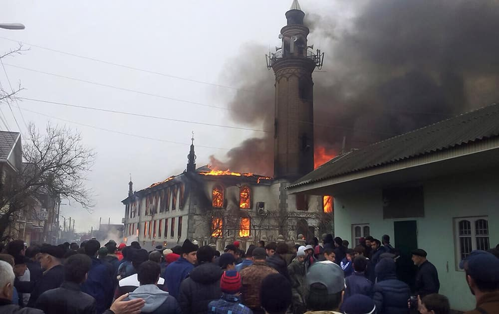People watch as black smoke and fire rising over the main mosque in Kizlyar, a town in the southern Russian republic of Dagestan.