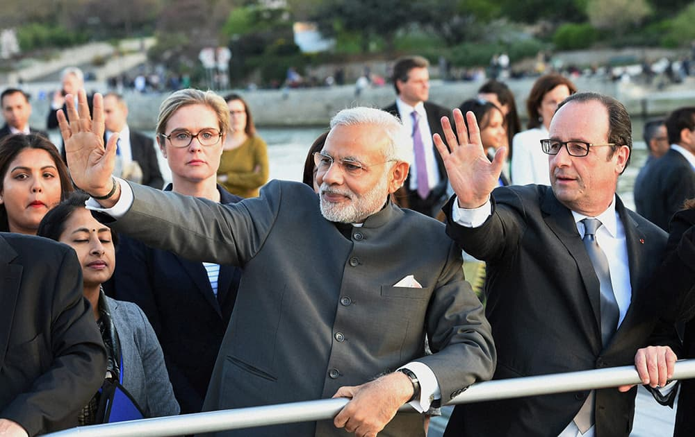 Prime Minister Narendra Modi with French President Francois Hollande wave during a boat ride on the Seine River, past the Eiffel Tower, in Paris.