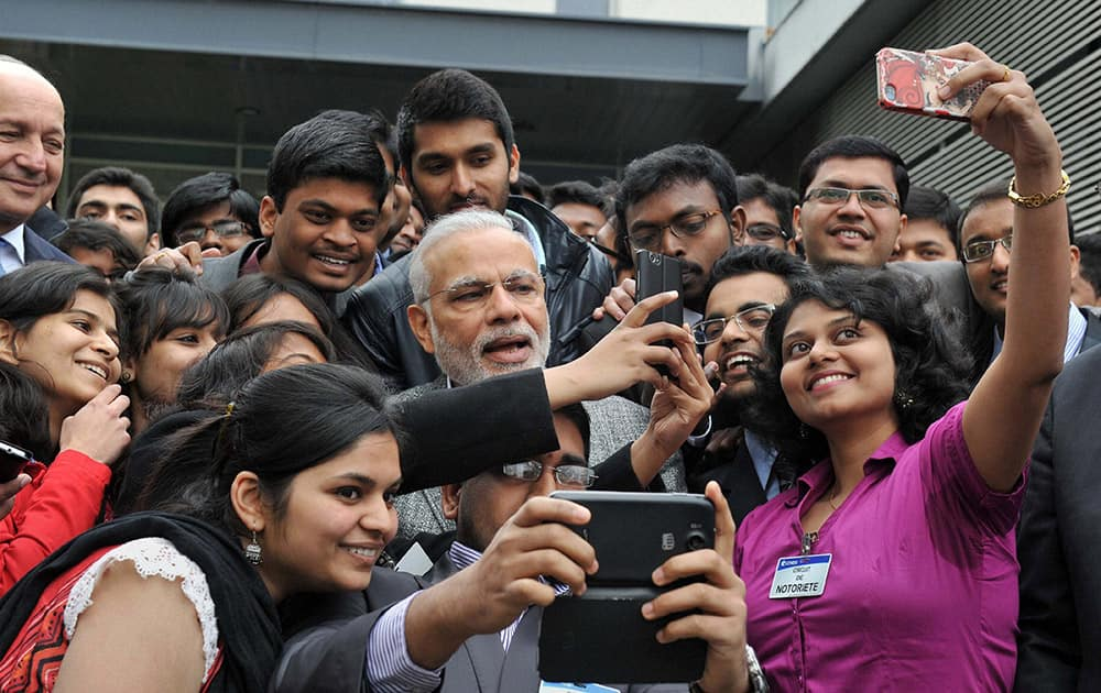 Prime Minister Narendra Modi takes a selfie with Indian employees during a visit to the Airbus facility in Toulouse, France.