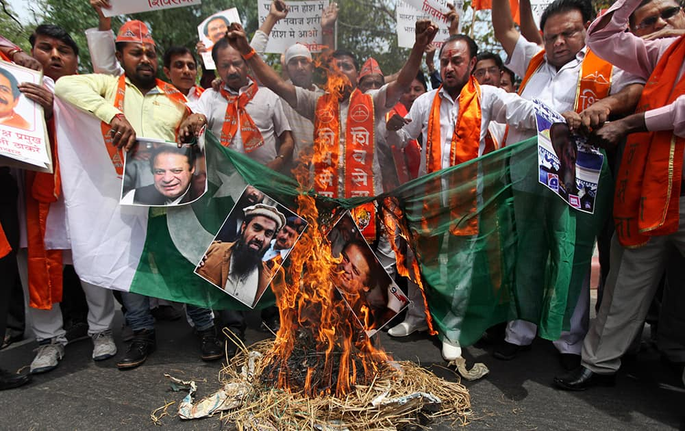 Shiv Sena activists burn a Pakistani flag along with posters of Pakistani Prime Minister Nawaz Sharif and suspected mastermind of the deadly Mumbai attacks in 2008 Zaki-ur-Rehman Lakhvi, after Lakhvi was released on bail by a Pakistani court, in New Delhi.