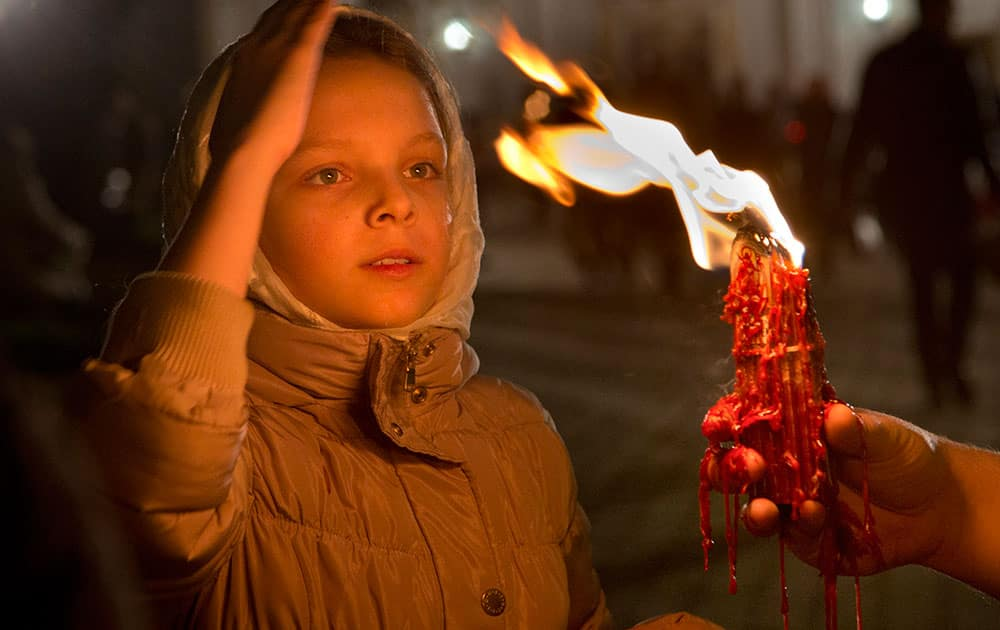 A girl blesses herself with the Holy Fire which was delivered to the Ukrainian capital from the Church of the Holy Sepulcher in Jerusalem's Old City, traditionally believed to be the burial place of Jesus Christ, after the ceremony of the Holy Fire on the Easter service in the Monastery of Caves in Kiev, Ukraine.