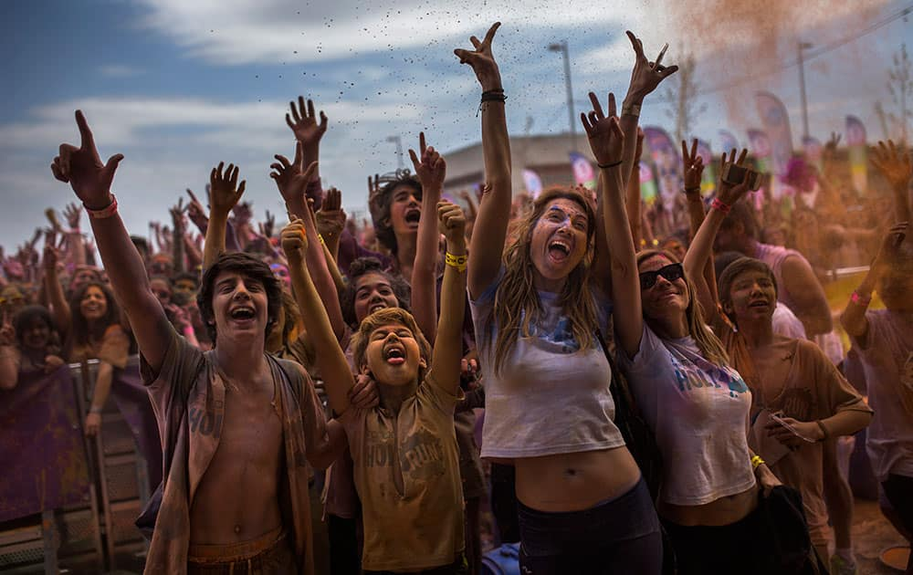 Revelers, covered in coloured powder, celebrate, during a Holi Run Festival in Madrid, Spain. Thousands of revelers took part in the festival that includes a mini marathon.