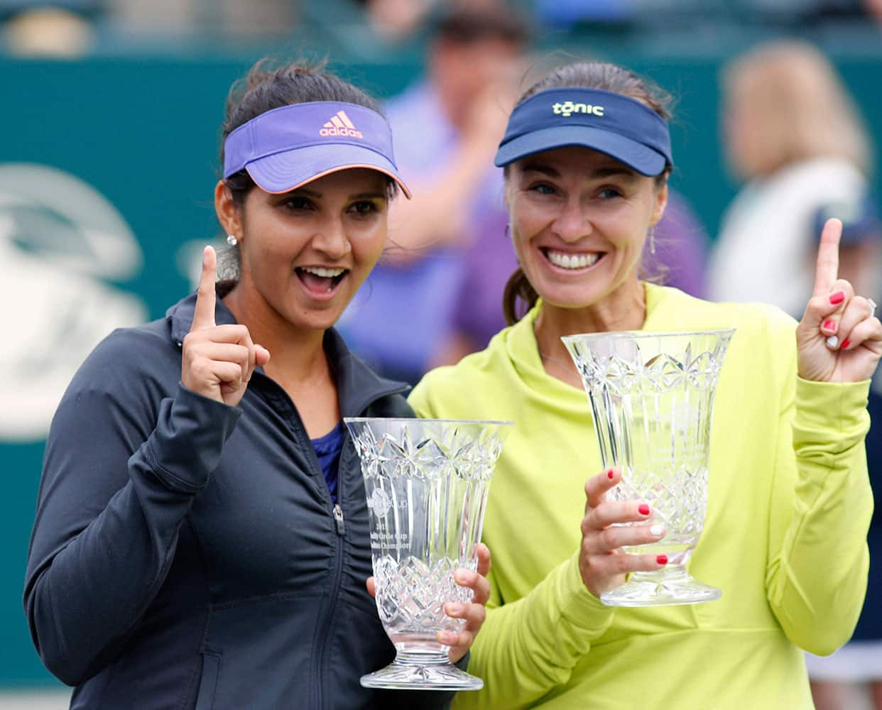 Sania Mirza of India, and her teammate, Martina Hingis of Switzerland, hold their trophies after defeating Alla Kudryavtseva and Anastasia Pavlyuchenkova during a doubles final match at the Family Circle Cup tennis tournament.
