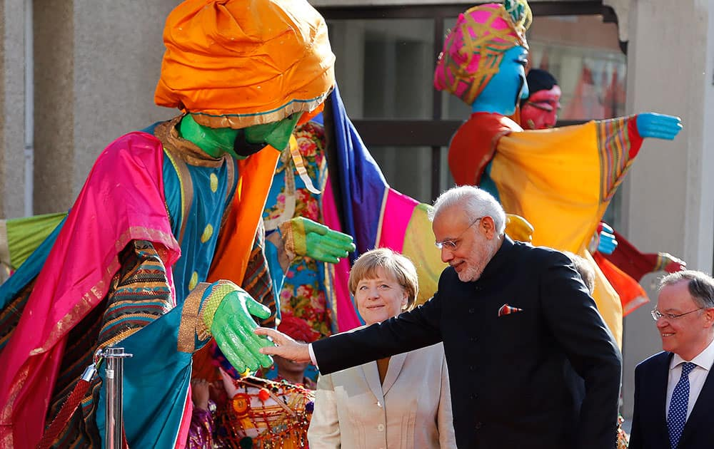 German Chancellor Angela Merkelwelcomes India's Prime Minister Narendra Modi as a traditional Indian music group performs at the opening of the industrial fair in Hanover, Germany.