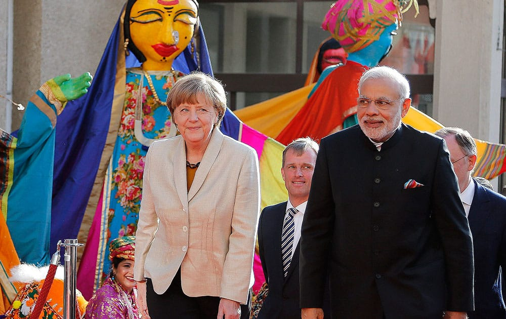 German Chancellor Angela Merkel, welcomes Indias Prime Minister Narendra Modi, as a traditional Indian music group performs at the opening of the industrial fair in Hanover, Germany.