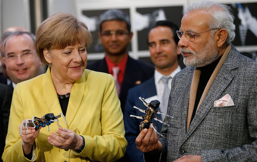 German Chancellor Angela Merkel and India's Prime Minister Narendra Modi hold bionic ants at the Festo company's booth during the opening of the industrial fair in Hanover, Germany.