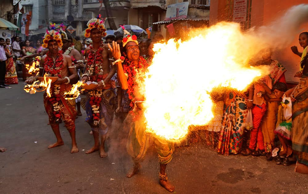 A Hindu devotee performs a fire act in a street during the Charak or the Shiva Gajan festival in Kolkata.