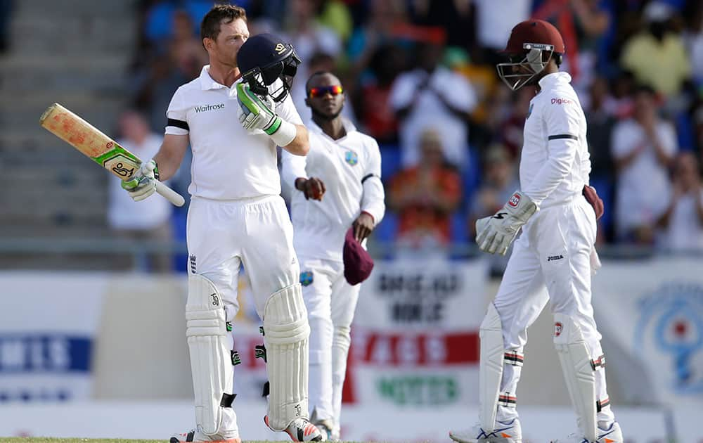 England's Ian Bell kisses his helmet after he scored a century, next to West Indies' Denesh Ramdin during the opening day of their first cricket Test match at the Sir Vivian Richards Cricket Ground in Antigua, Antigua and Barbuda.