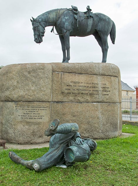 This picture taken on Tuesday, April, 7, 2015, a statue of a British soldier lays on the ground after being broken off it's base in Port Elizabeth, South Africa. Excrement thrown at the statue of British colonialist Cecil John Rhodes began a wave of vandalizing protests in South Africa.