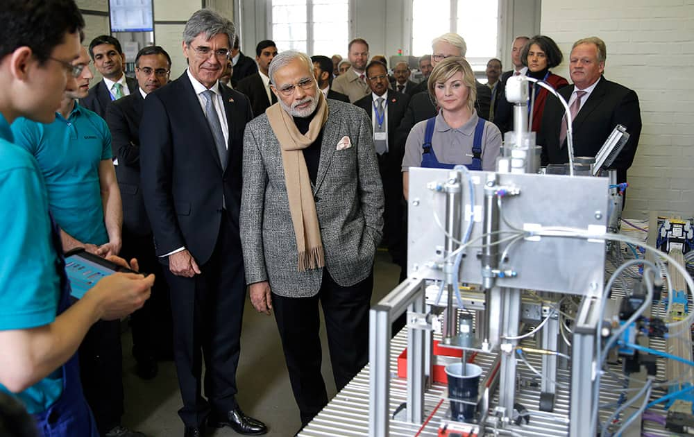 Prime Minister of India, Narendra Modi and Siemens CEO Joe Kaeser, look at a 'coffee machine' build by trainees during a visit of the Siemens company in Berlin, Germany.
