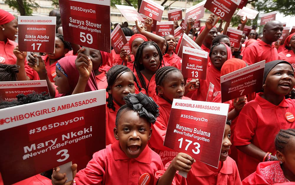 Young girls known as Chibok Ambassadors, carry placards bearing the names of the girls kidnapped from the government secondary school in Chibok, a year ago, during a demonstration, in Abuja, Nigeria.