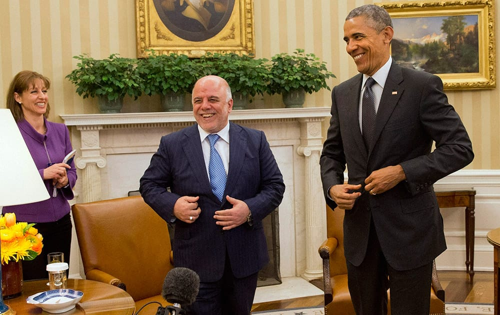Iraqi Prime Minister Haider Al-Abadi and President Barack Obama fix their suit jackets as they finish their meeting in the Oval Office of the White House in Washington.