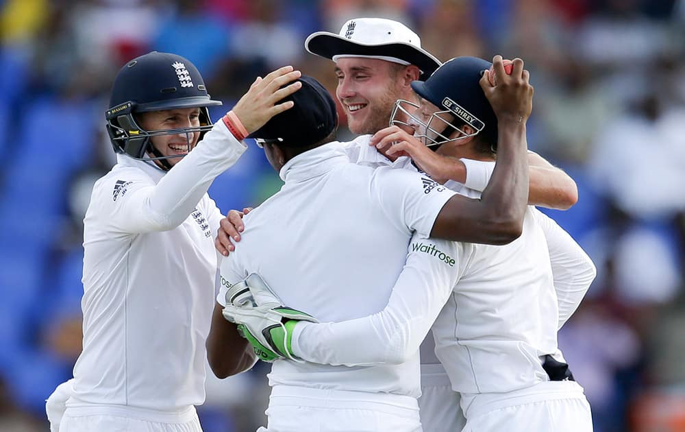 England's Joe Root, Stuart Broad and Jos Buttler embrace teammate Chris Jordan, back to the camera, after he caught West Indies' Kraigg Brathwaite during the second day of their first cricket Test match at the Sir Vivian Richards Cricket Ground in Antigua, Antigua and Barbuda.
