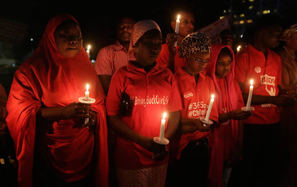 People hold candles during a vigil to mark the one year anniversary of the abduction of girls studying at the Chibok government secondary school, Abuja, Nigeria.