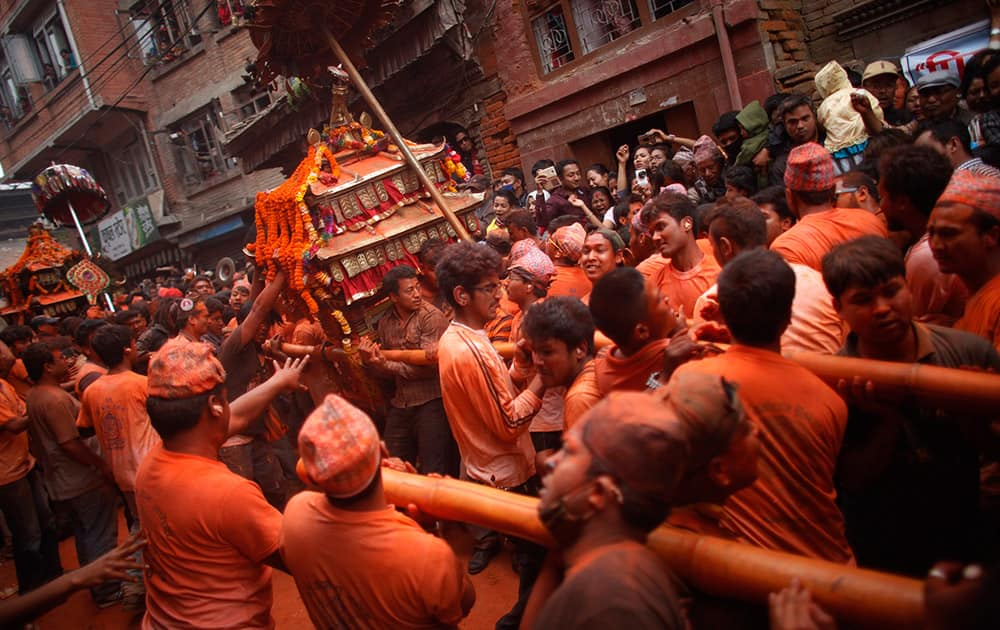 Nepalese devotees, covered in color vermilion powder, carry a palanquin with idols of Hindu deities during Sindur Jatra festival in Thimi, outskirts of Kathmandu, Nepal.