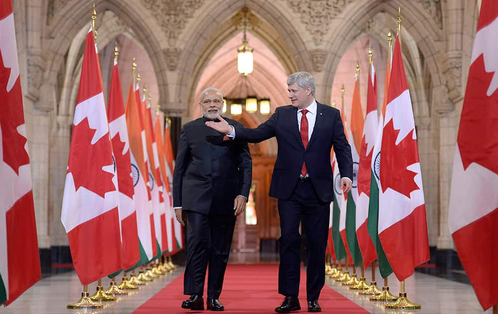 Prime Minister Narendra Modi and Canadian Prime Minister Stephen Harper walk down the Hall of Honor on Parliament Hill in Ottawa.