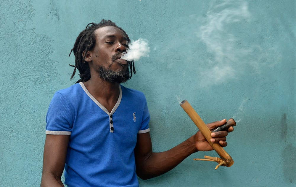 A Jamaican Rastafarian known as Nature smokes marijuana outside the Trench Town Culture Yard Museum in downtown Kingston, Jamaica.