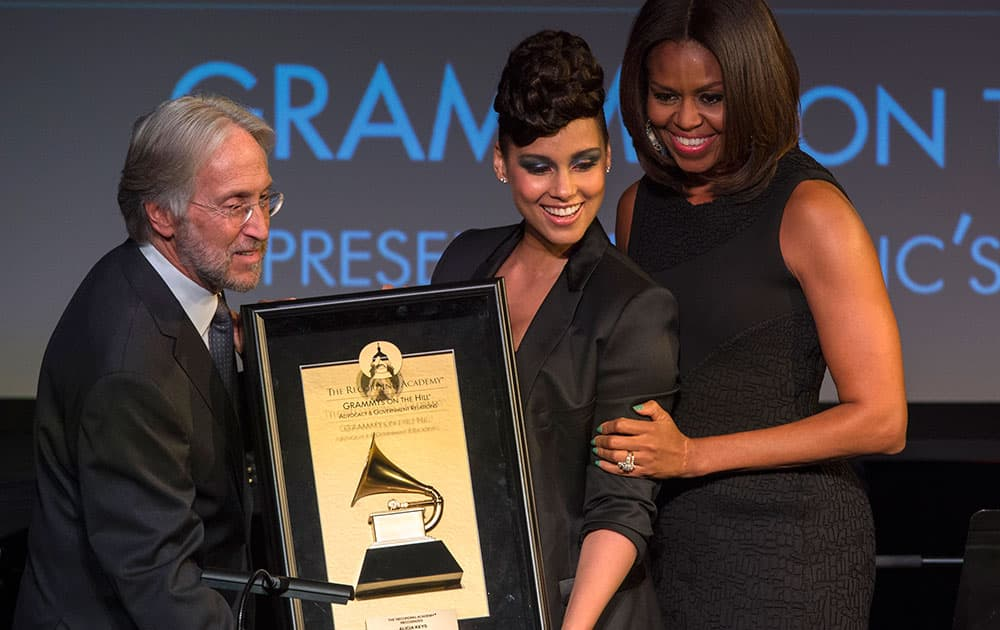 First lady Michelle Obama, along with Recording Academy President and CEO Neil Portnow, awards 15-time Grammy winner Alicia Keys the Recording Academy's Recording Artists' Coalition Award at the Grammys On The Hill Awards in Washington.