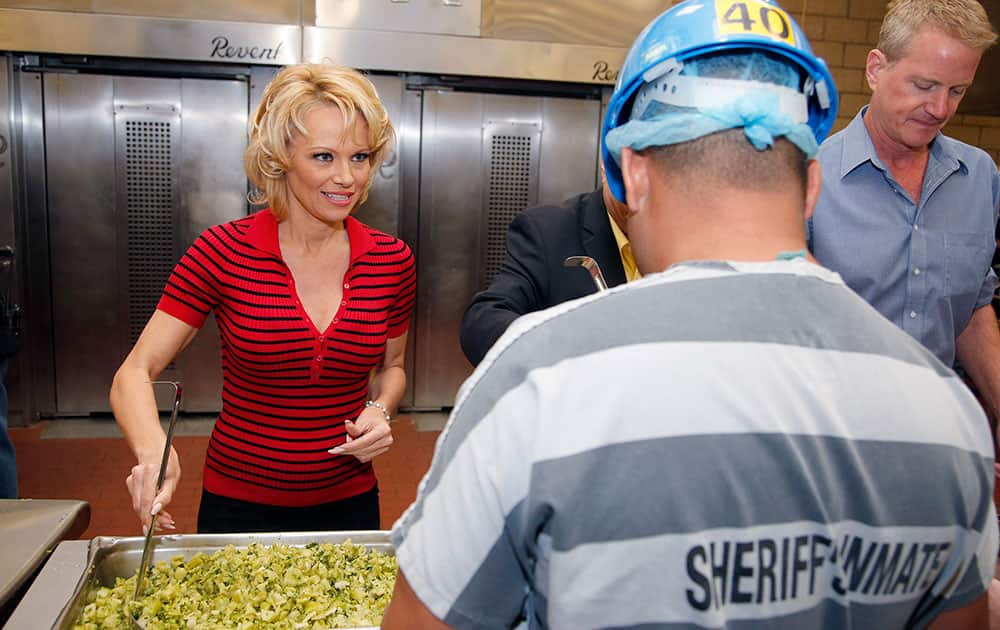 Actress Pamela Anderson, left, serves steamed broccoli to an inmate as part of an all-vegetarian meal at the Maricopa County Jail, making it the first jail in the country to go entirely vegetarian, in Phoenix.