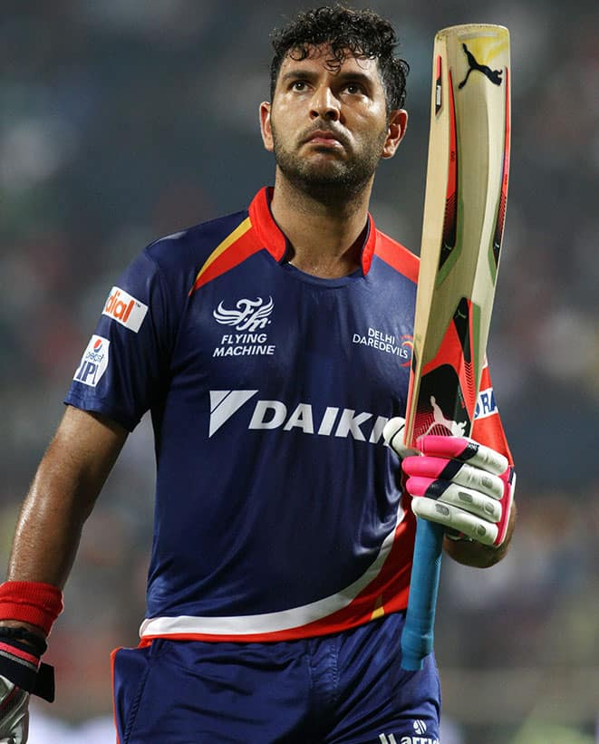 Delhi Daredevils player Yuvraj Singh raises his bat as he walks back to the pavilion after getting out during an IPL T20 match against Kings XI Punjab in Pune.