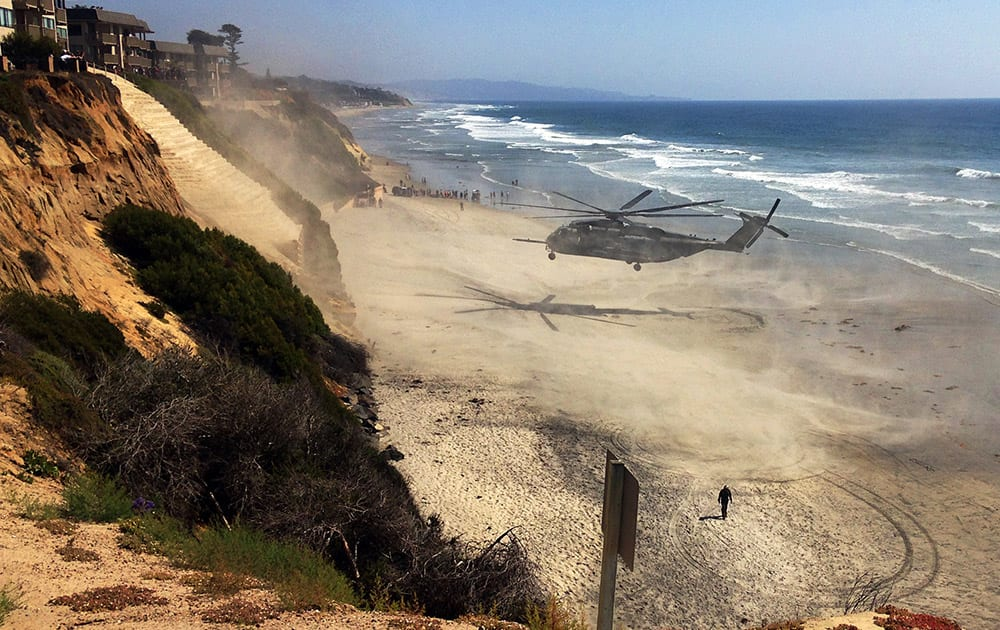 A Marine Corps helicopter lifts off from the beach after it made an emergency landing Wednesday, April 15, 2015, in Solana Beach, Calif. The helicopter landed on the shore shortly after 11:30 a.m. after a low oil-pressure indicator light went on in the cockpit, Marine Corps Air Station Miramar said in a statement.