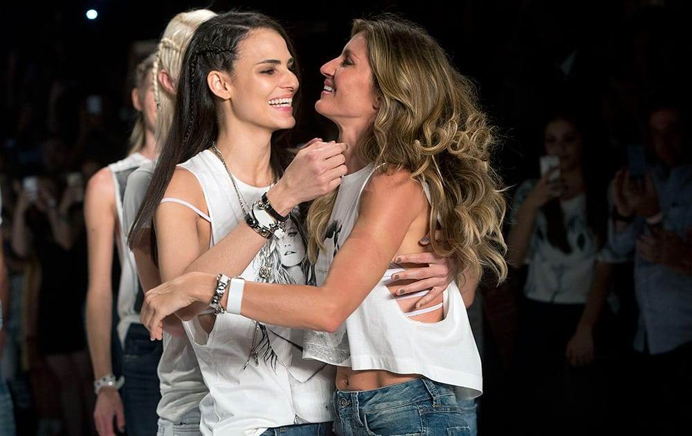 Brazilian supermodel Gisele Bundchen, right, and fellow Brazilian model Fernanda Tavares embrace at the end of the show from the Colcci Summer collection, at the Sao Paulo Fashion Week in Sao Paulo, Brazil.