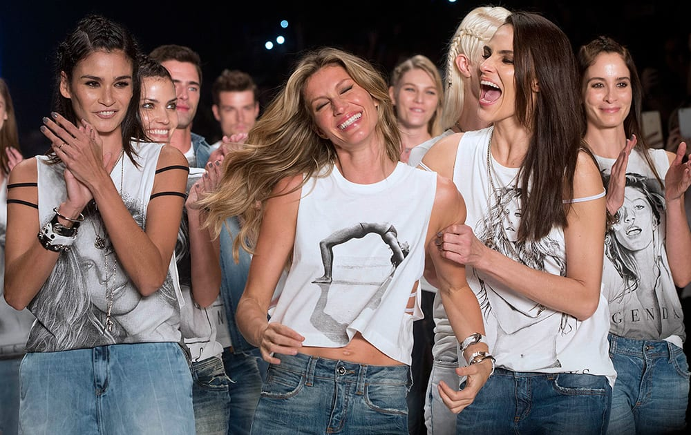 Brazilian supermodel Gisele Bundchen, celebrates with models Caroline Ribeiro and Fernanda Tavares, right, at the end of the show from the Colcci Summer collection at Sao Paulo Fashion Week in Sao Paulo, Brazil.