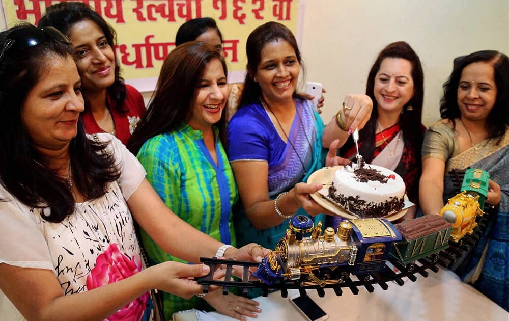 Women commuters cut a huge cake modeled on the Thane railway station on the occasion of its 162nd anniversary at Thane, Mumbai.