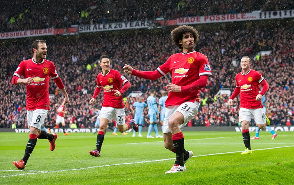 Manchester United's Marouane Fellaini, celebrates after scoring during the English Premier League soccer match between Manchester United and Manchester City at Old Trafford Stadium.