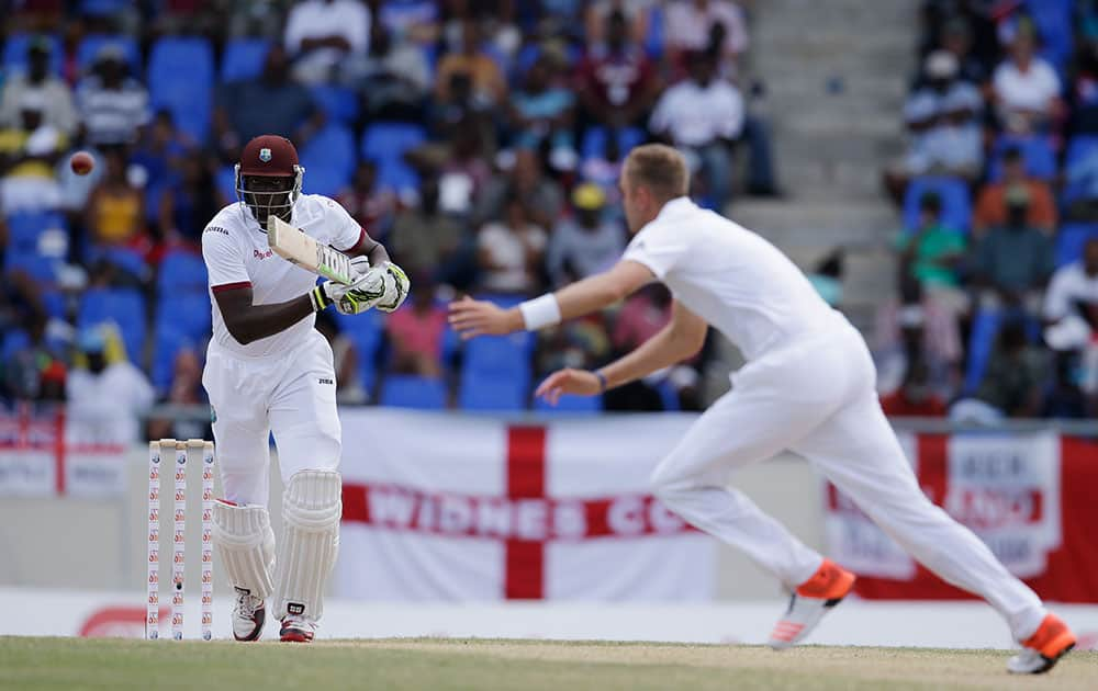 West Indies' Jason Holder, left, plays a shot from the bowling of England's Stuart Broad, during the last day of their first cricket Test match at the Sir Vivian Richards Cricket Ground in Antigua, Antigua and Barbuda.