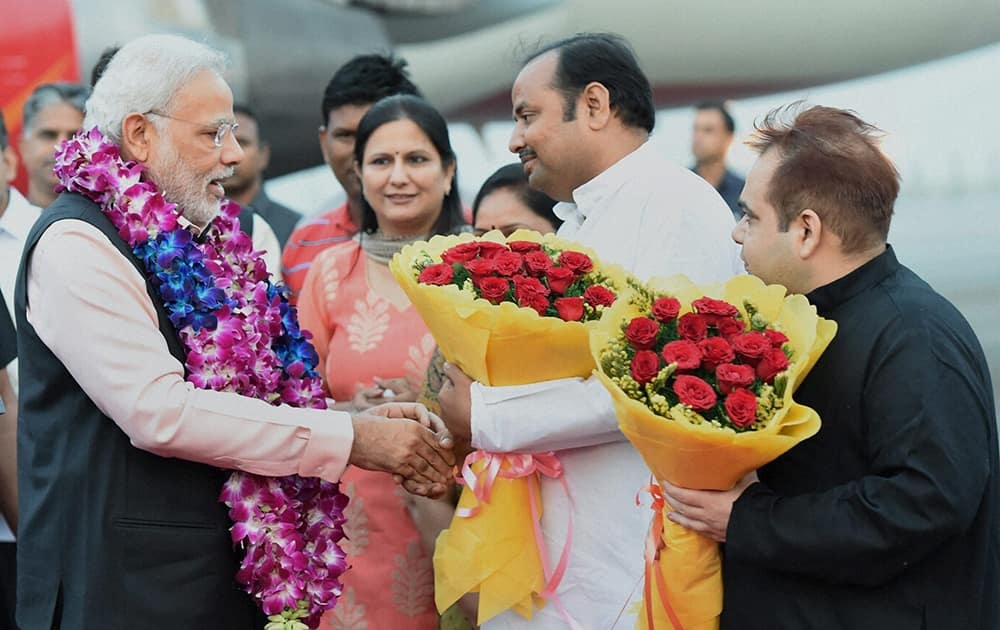 Prime Minister Narendra Modi being welcomed upon arrival after a three nation tour at Air Force station Palam, in New Delhi.