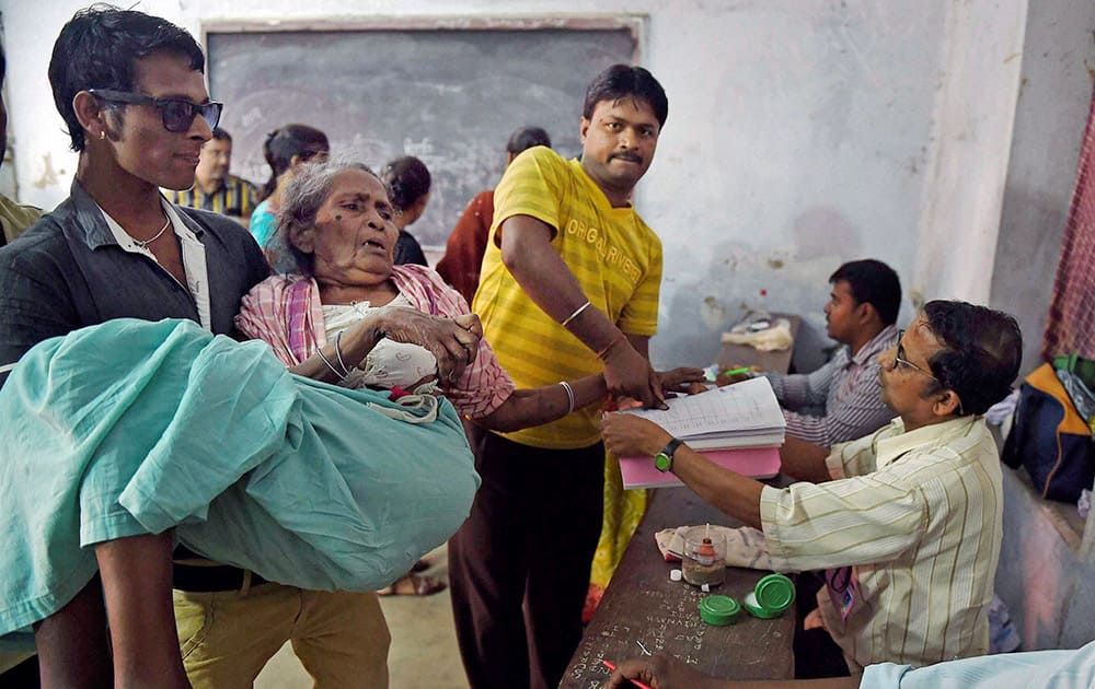 An elderly woman castes her vote with the assistance of family members and polling officers during the Municipal Corporation elections.