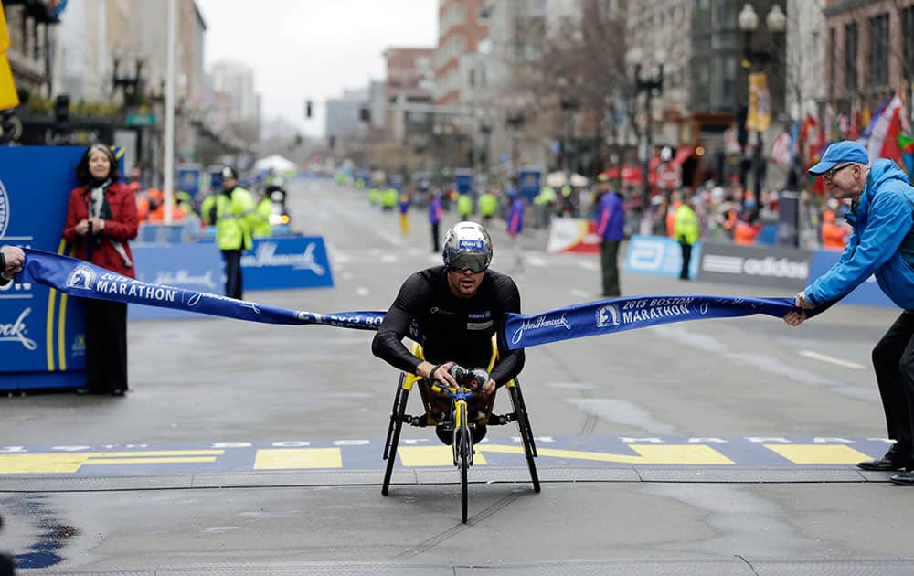 Marcel Hug, of Switzerland, breaks the tape at the finish line to win the wheelchair division of the Boston Marathon.
