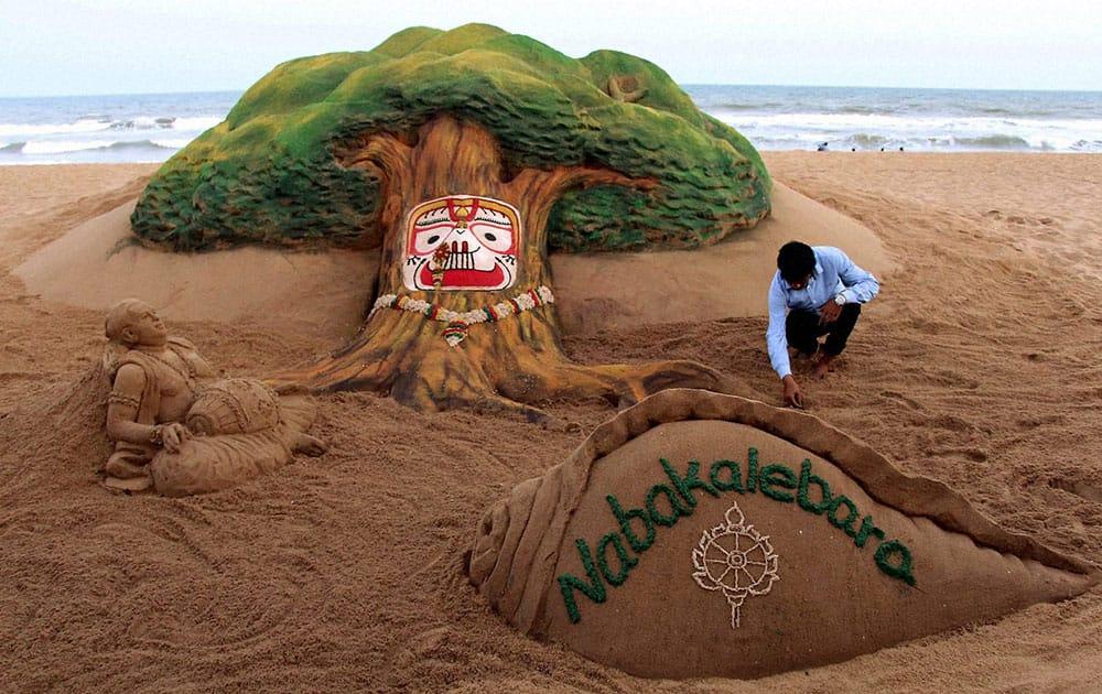 Sand artist Sudarsan Pattnaik creates a sand sculpture on Nabakalebara at Puri beach of Odisha.