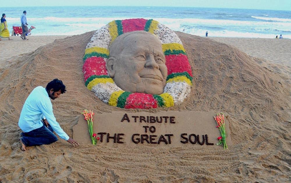 Sand artist Sudarsan Pattnaik creates a sand sculpture to pay tribute Odishas former chief minister JB Pattanaik at Puri beach.