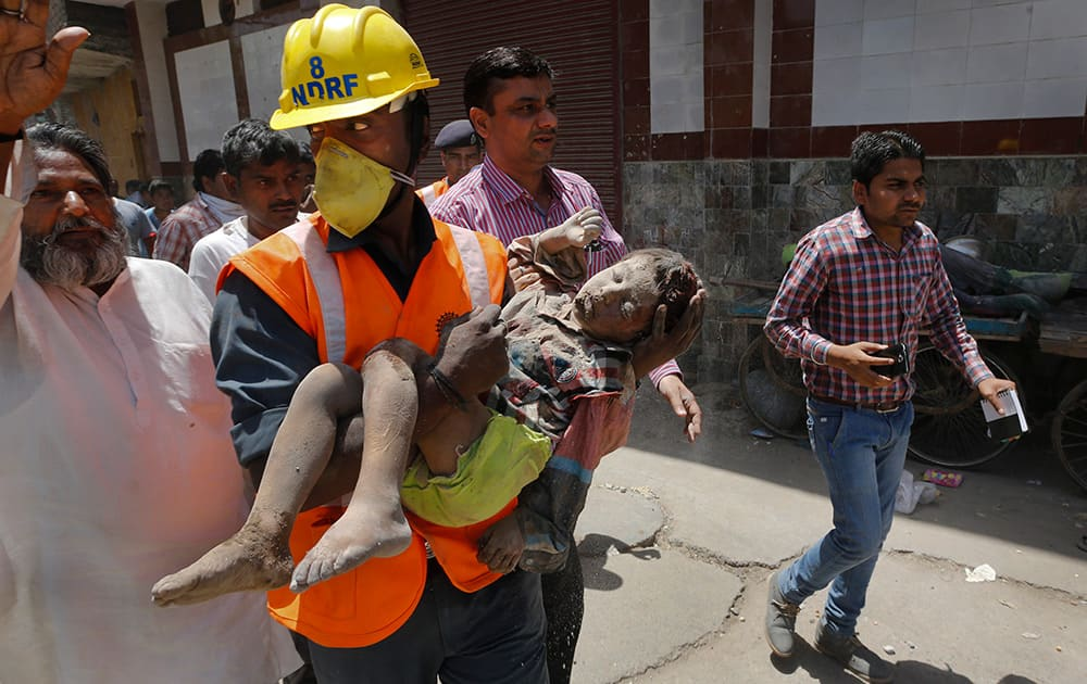 A members of National Disaster Response Force carries an injured child, found under the debris of a residential building, to an ambulance, in New Delhi. One man and a child were killed and at least nine others were injured when a three-storey residential building collapsed following an explosion in a cooking gas cylinder.