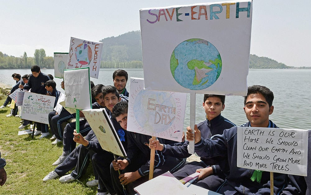 School children hold placards sitting on the banks of Dal Lake to mark World Earth Day.
