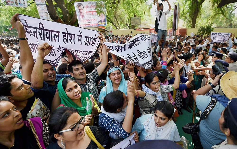 Contractual teachers shout slogans and display banners against Delhi CM Arvind Kejriwal during Aam Aadmi Party (AAP)s rally against the Union governments Land Acquisition Bill at Jantar Mantar in New Delhi.