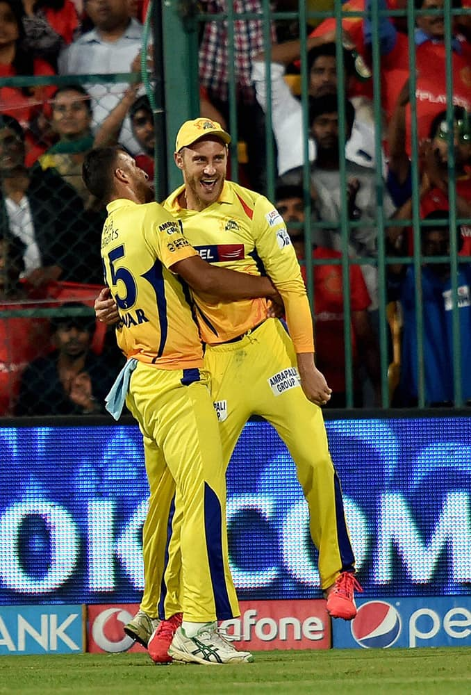 Chennai Super Kings Faf Du Plesis with Suresh Raina after taking a sucessful catch of Manvender Bisla during IPL 8 against Royal Challengers Bangalore match at Bengaluru.