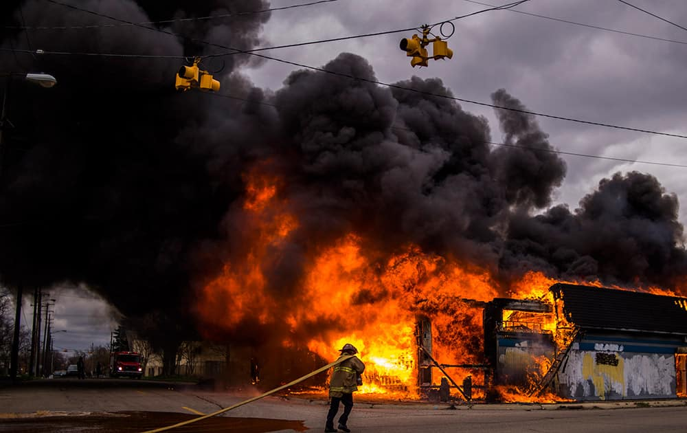 Flint firefighters work to contain a large fire that engulfs a former strip club, once called The Body Shop at the intersection of Glenwood Avenue and Asylum Street, sending a large plume of black smoke over the city of Flint, Mich.