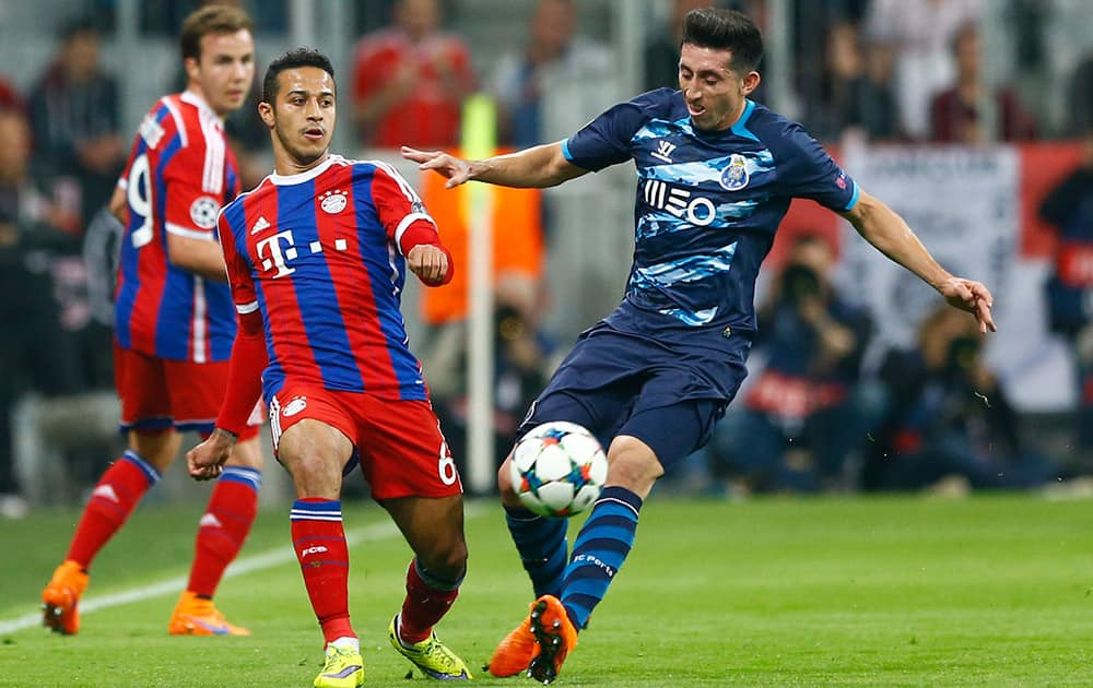 Bayern's Thiago, left, and Porto's Hector Herrera challenge for the ball during the soccer Champions League quarterfinal second leg match between Bayern Munich and FC Porto at the Allianz Arena in Munich, southern Germany.