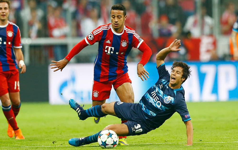 Bayern's Thiago, left, and Porto's Oliver Torres challenge for the ball during the soccer Champions League quarterfinal second leg match between Bayern Munich and FC Porto at the Allianz Arena in Munich, southern Germany.