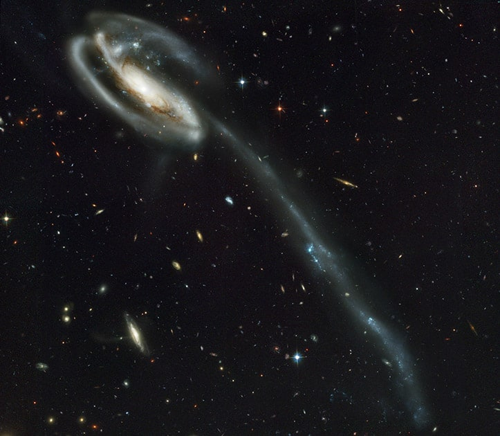 This image made by the NASA/ESA Hubble Space Telescope shows galaxy UGC 10214 with the long streamer of stars. Its distorted shape was caused by another galaxy passing nearby. The Hubble Space Telescope marks its 25th anniversary.