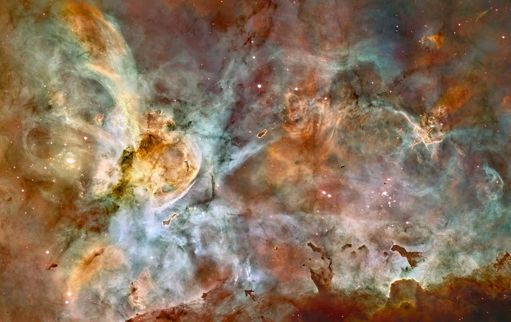 This false-color image made by the NASA/ESA Hubble Space Telescope shows the Carina Nebula. Outflowing winds and intense ultraviolet radiation from the large stars shape the material that is the last vestige of the giant cloud from which the stars were born. Red corresponds to sulfur, green to hydrogen, and blue to oxygen emission. The Hubble Space Telescope marks its 25th anniversary.