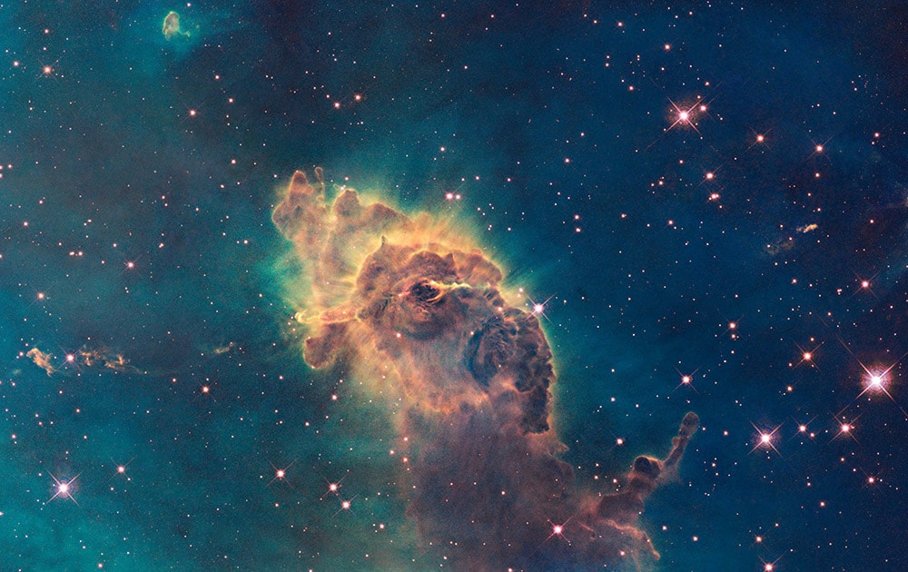 This image made by the NASA/ESA Hubble Space Telescope shows the tip of the three-light-year-long pillar in a stellar nursery called the Carina Nebula, located 7500 light-years away from the Earth. Composed of gas and dust, the structure is illuminated by light from hot, massive stars off the top of the image. The Hubble Space Telescope marks its 25th anniversary.