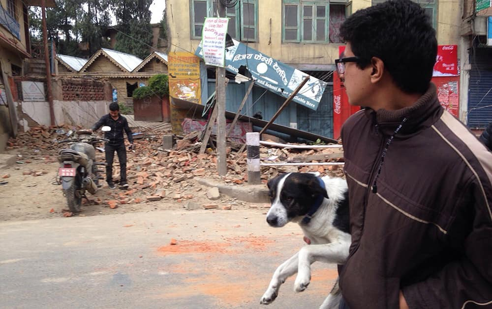 A man carries a dog and walks past damage caused by an earthquake in Kathmandu, Nepal. A strong magnitude-7.9 earthquake shook Nepal's capital and the densely populated Kathmandu Valley before noon Saturday, causing extensive damage with toppled walls and collapsed buildings, officials said.