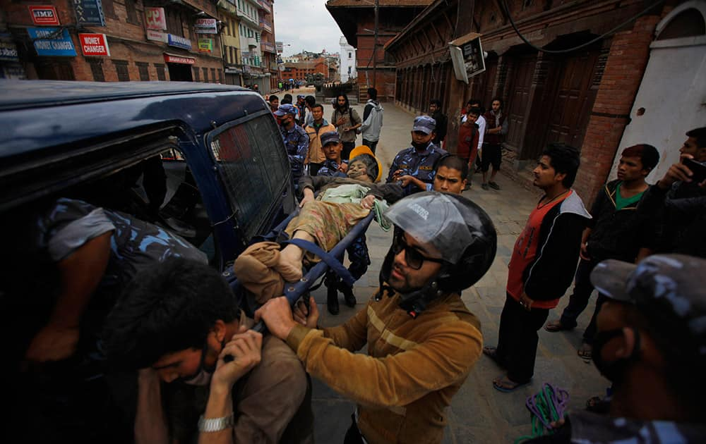 Volunteers carry an injured woman after an earthquake in Kathmandu, Nepal. A strong magnitude-7.9 earthquake shook Nepal's capital and the densely populated Kathmandu Valley before noon Saturday, causing extensive damage with toppled walls and collapsed buildings, officials said.